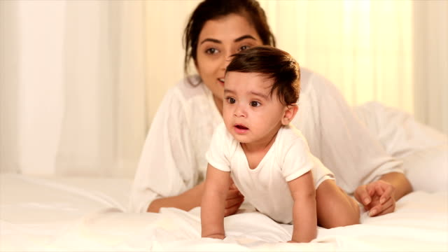 ms pan baby girl crawling on bed while mother in background / delhi, india - crawling stock videos & royalty-free footage