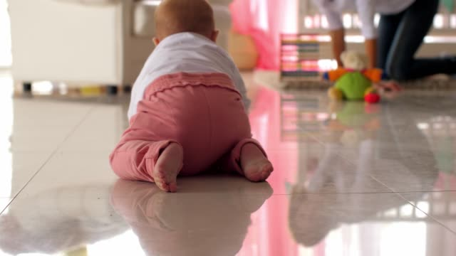 baby girl crawling on the nursery floor while playing with her mother - crawling stock videos & royalty-free footage
