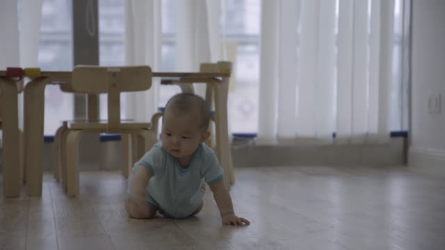 r/t ms baby girl crawling on wooden floor at home / chongqing, china - 這う点の映像素材/bロール