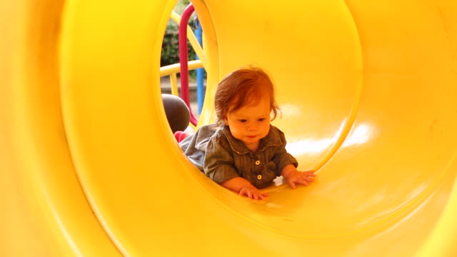 a baby girl crawling through a yellow tunnel. - krabbeln stock-videos und b-roll-filmmaterial