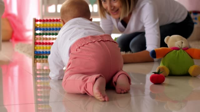 baby girl crawling to get a toy from her mother - crawling stock videos & royalty-free footage