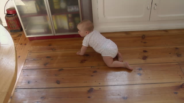vídeos y material grabado en eventos de stock de ms ha pan zi baby girl (6-11 months) crawling towards kitchen cabinet then sitting and looking at camera, berlin, germany - pijama de una pieza