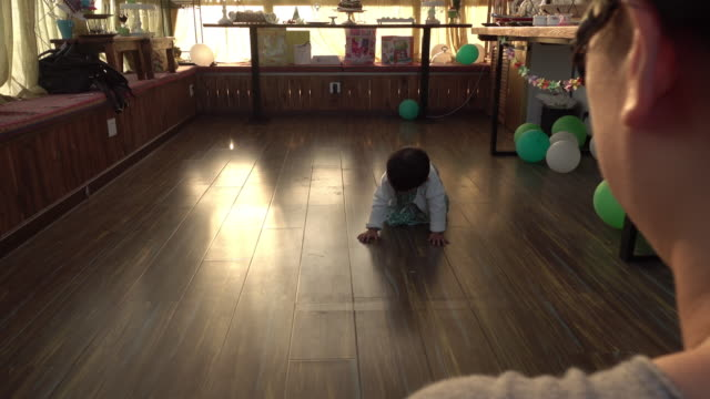 A baby girl crawling towards mother