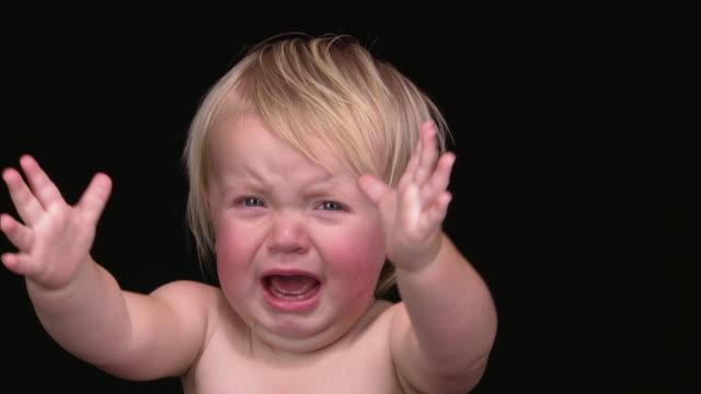 vídeos de stock e filmes b-roll de cu portrait baby girl crying and messing hair with hands/ england - bebés meninas