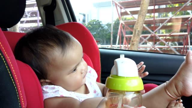 女の赤ちゃんは、車の安全シートに水を飲むことを否定します - 断る点の映像素材/bロール