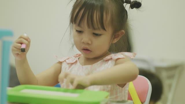 赤ちゃんの女の子は宿題 - 片付いた部屋点の映像素材/bロール
