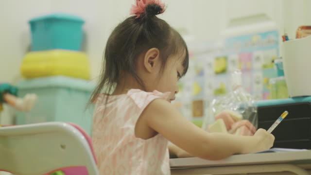 宿題をしている女の赤ちゃん - 片付いた部屋点の映像素材/bロール