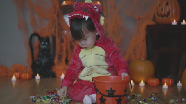 baby girl dressed up playing at halloween party - confectionery stock videos & royalty-free footage
