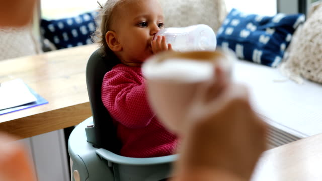 baby girl drinking milk from bottle in play cafe - milk stock videos & royalty-free footage