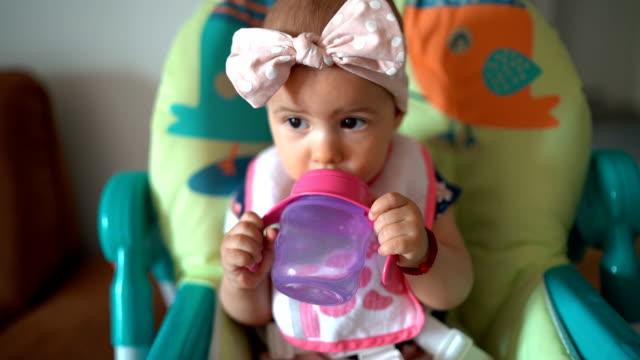 baby mädchen trinkwasser in einem hochstuhl - weibliches baby stock-videos und b-roll-filmmaterial