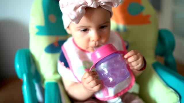 bebis flicka dricks vatten i en barnstol - endast en flickbaby bildbanksvideor och videomaterial från bakom kulisserna