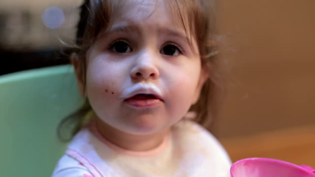 baby girl drinking yogurt on her own - moustache stock videos & royalty-free footage