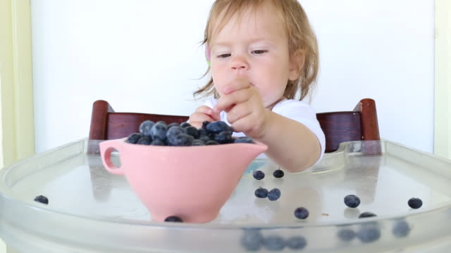 A baby girl eating blueberries and cheese in a high chair outdoors on a porch.