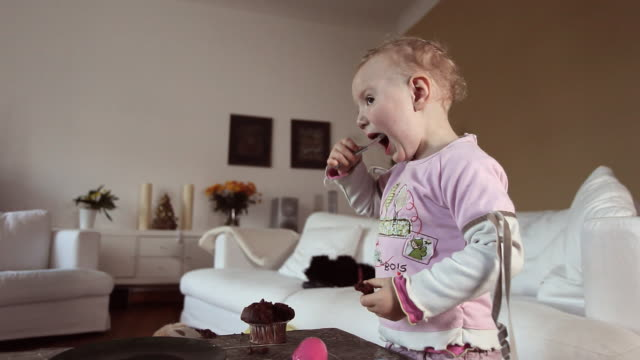 MS Baby girl (12-23 months) eating cupcake in living room / Potsdam, Brandenburg, Germany