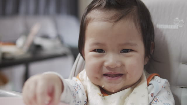 vídeos de stock, filmes e b-roll de menina comendo comendo comida alimentando por sua mãe na sala de estar em casa. - alimentando