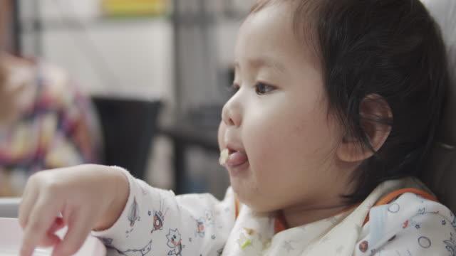 vídeos y material grabado en eventos de stock de niña alimentada por su madre. - cereal de desayuno