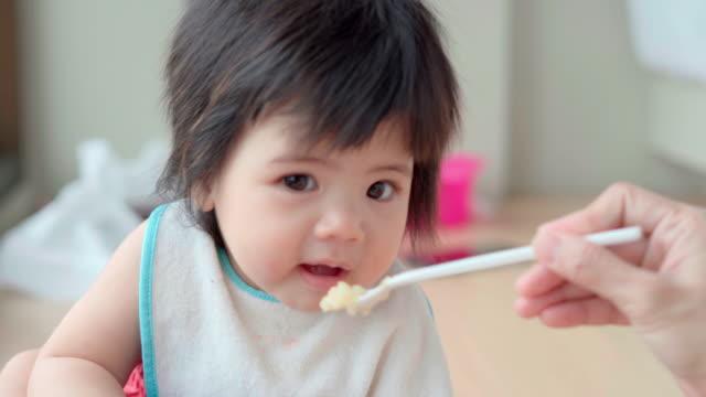 vídeos de stock, filmes e b-roll de menina comendo comida - boca humana
