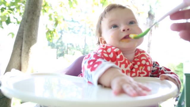 A baby girl eating from a spoon outside in a hi chair.