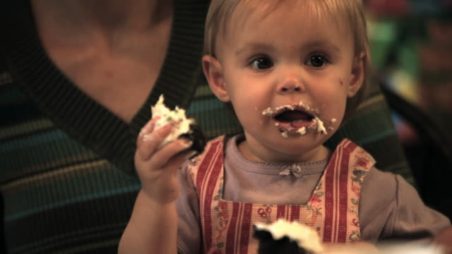 ms baby girl (12-17 months) eating icing off cupcake with her hands sitting on mother's lap / norwich, vermont, usa - sideways glance stock videos & royalty-free footage