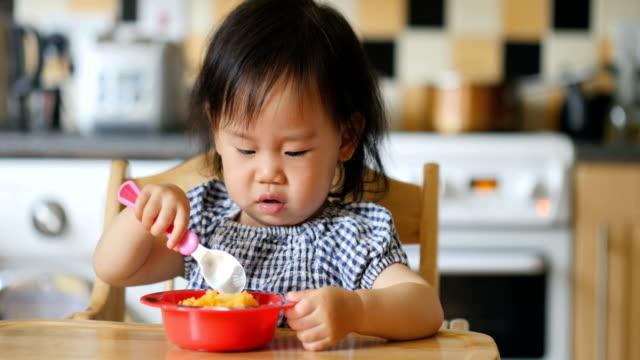 vídeos de stock, filmes e b-roll de menina comendo purê de batata - cadeirinha cadeira