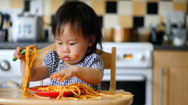 vídeos y material grabado en eventos de stock de niña comiendo espagueti sucio - comida de bebé
