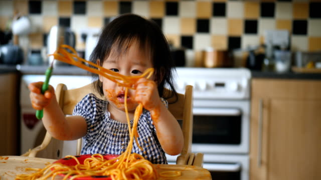 baby girl eating messy spaghetti - messy stock videos & royalty-free footage
