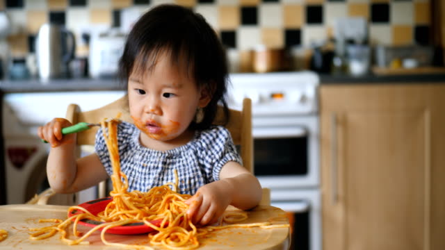 baby girl eating messy spaghetti - spaghetti stock videos & royalty-free footage
