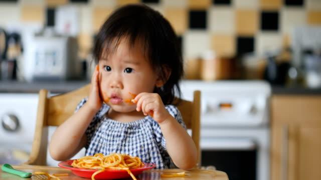 baby girl eating messy spaghetti - salsa di pomodoro video stock e b–roll