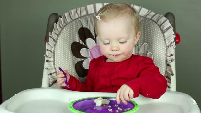 vídeos de stock, filmes e b-roll de bebê menina comendo na cadeira alta - cadeirinha cadeira