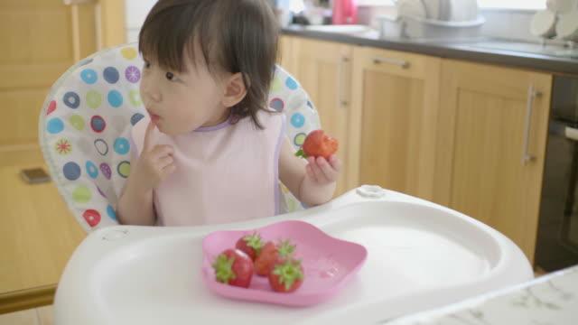 vídeos de stock, filmes e b-roll de menina comendo morango - cadeirinha cadeira