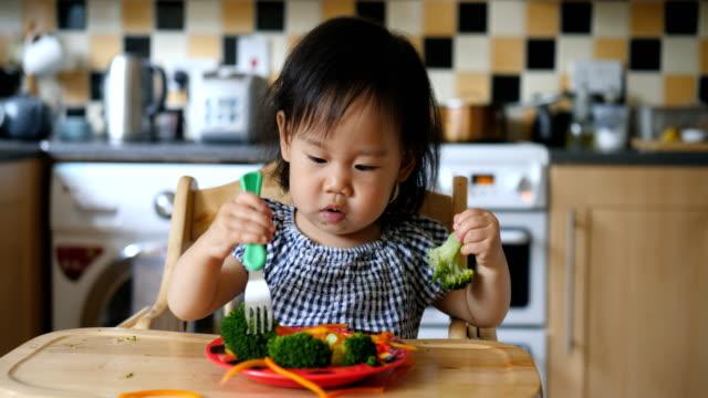 vídeos y material grabado en eventos de stock de niña comiendo vegetales - comida de bebé