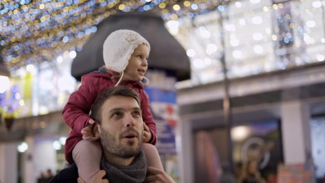 baby girl enjoying christmas lights on dad's back - family back lit stock videos & royalty-free footage