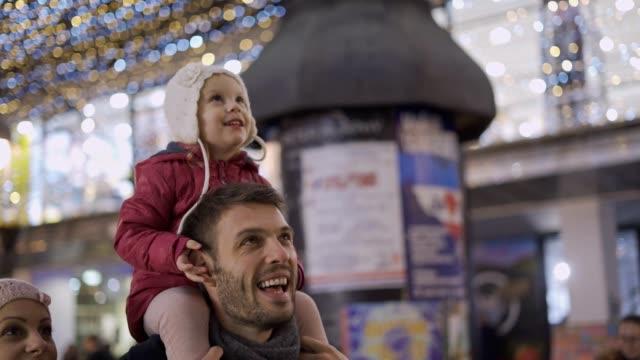 babymädchen genießen weihnachten lichter auf papas rücken - körperliche aktivität stock-videos und b-roll-filmmaterial