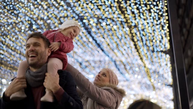 babymädchen genießen weihnachten lichter auf papas rücken - back lit stock-videos und b-roll-filmmaterial