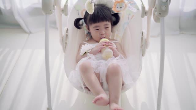 stockvideo's en b-roll-footage met baby girl enjoying her sister's rocking chair - schommelen schommelstoel