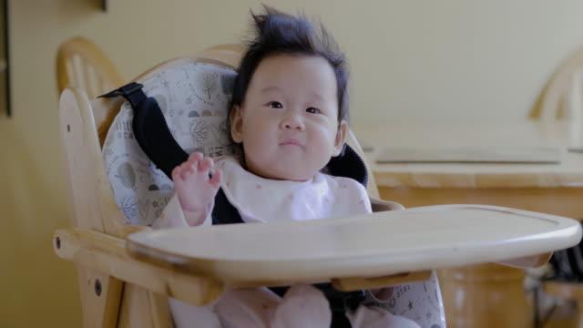 vídeos de stock, filmes e b-roll de menina primeira vez comendo alimentos sólidos - comida de bebê