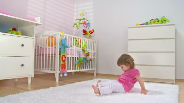 vídeos de stock e filmes b-roll de grou de hd: bebê menina divertir-se no tapete - cair