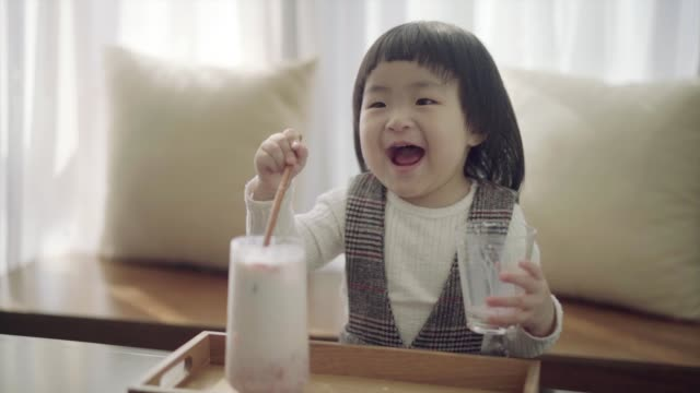 baby girl having fun with glass of strawberry milk in the livingroom. - spoon stock videos & royalty-free footage