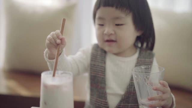 vídeos y material grabado en eventos de stock de baby girl having fun with glass of strawberry milk in the livingroom. - cuchara