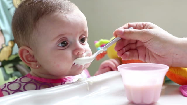 a baby girl having her first milk and food - food state stock videos & royalty-free footage
