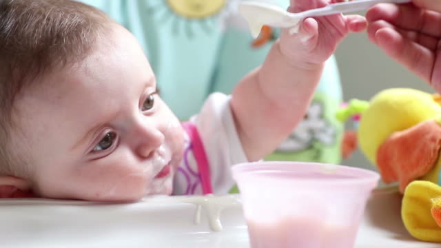 A baby girl having her first milk and food