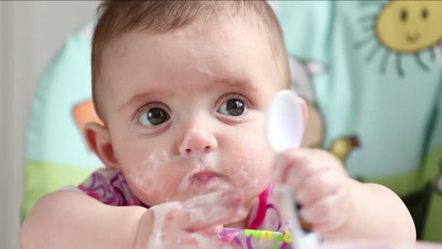 vidéos et rushes de a baby girl having her first milk and food - vêtement de bébé
