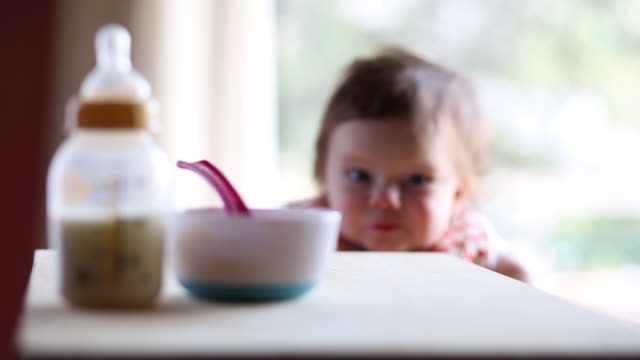 a baby girl having milk and food inside of a house during the day. - one baby girl only stock videos & royalty-free footage