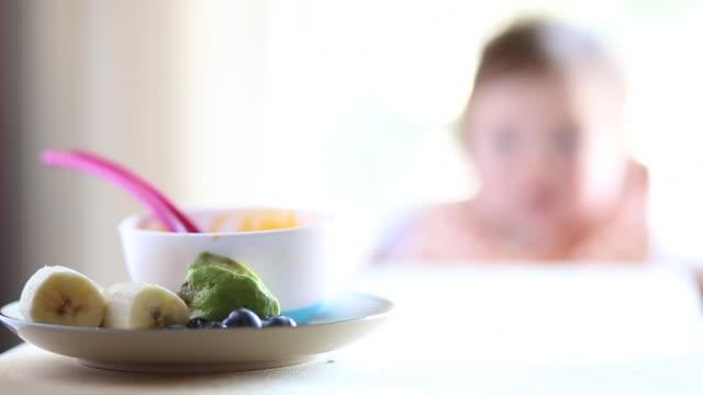 vídeos y material grabado en eventos de stock de a baby girl having milk and food inside of a house during the day. - comida de bebé