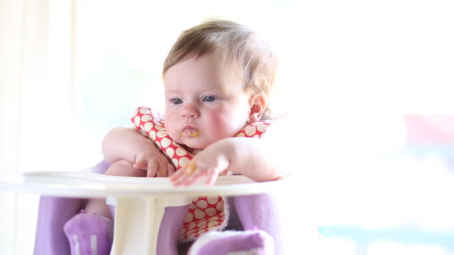 a baby girl having milk and food inside of a house during the day. - weibliches baby stock-videos und b-roll-filmmaterial