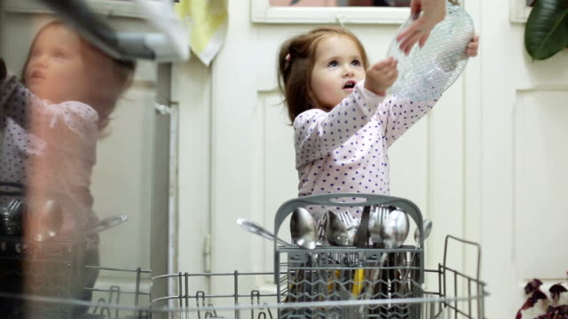 baby girl helping her mother with dishes - lavastoviglie video stock e b–roll