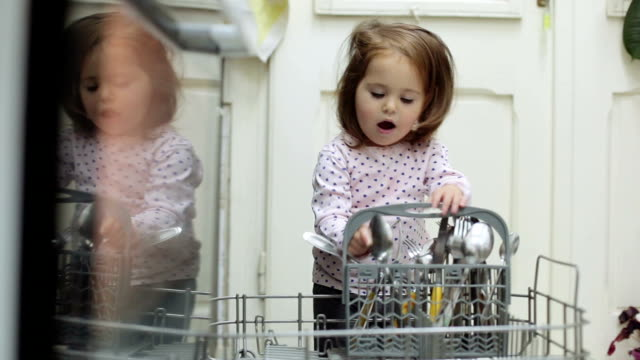 baby girl helping her mother with dishes