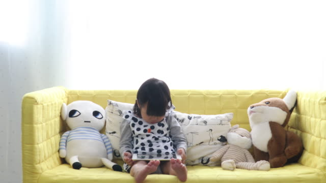 baby girl holding a tablet and sits on sofa - one baby girl only stock videos and b-roll footage