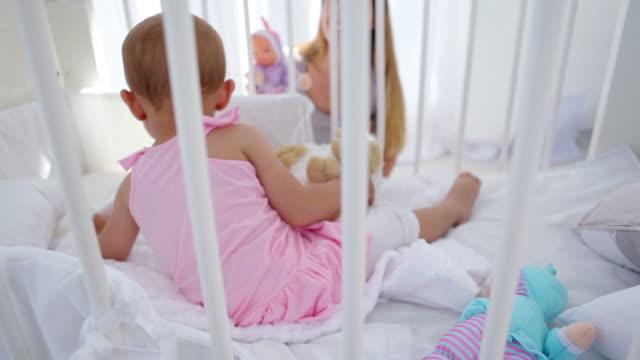 vidéos et rushes de baby girl in a cradle playing with her mother - vêtement de bébé