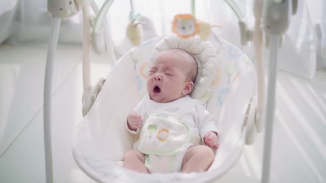 baby girl in her rocking chair - dondolarsi video stock e b–roll